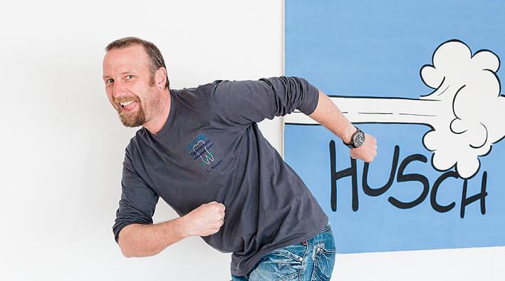 Herr Opfermann in Renn-Position vor einem 'Husch'-Plakat